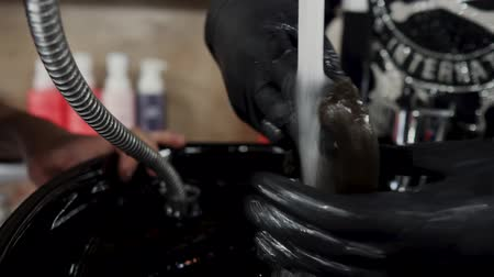 saç kremi : Hairdresser washes a strand of hair under the tap for hair extensions. 4K
