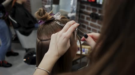 основа : The hairdresser sews artificial hair to the real thing. The process of hair extension. 4K