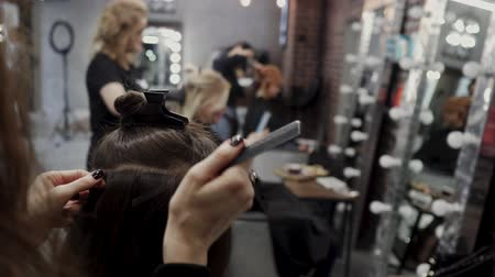 kiterjesztés : The hairdresser sticks the artificial hair to the real thing. The process of hair extension. 4K
