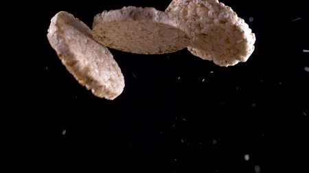rice cake : Three rice and corn bread fly up on a black background. Slow motion Stock Footage