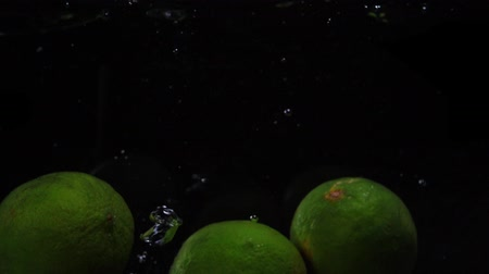 lyme : Three green lines are thrown into a container of water. Video of fruit in slow motion. Food video.