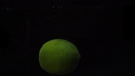 lyme : Green lime are thrown into a container of water. Video of fruit in slow motion. Food video.
