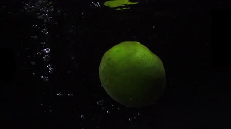 охлажденный : Green lime are thrown into a container of water. Video of fruit in slow motion. Food video.