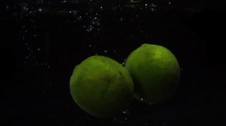 охлажденный : Two green lime are thrown into a container of water. Video of fruit in slow motion. Food video. Стоковые видеозаписи
