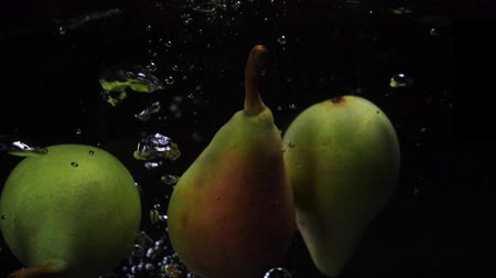 погружение : Three pears falls into the water with splashes and bubbles in slow motion.