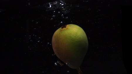 immersione : One pear falls into the water with splashes and bubbles in slow motion.