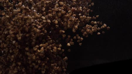 grano saraceno : Buckwheat falls into water. Underwater shooting of buckwheat. Slow motion. Food video
