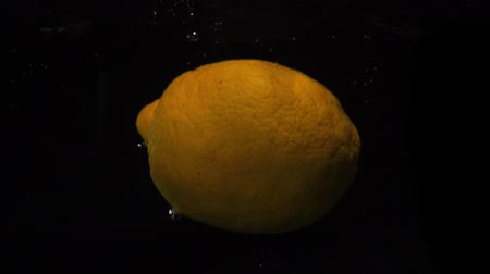 banheira : Yellow lemon falls into water on black background. Slow motion macro shot. Food video lemon Vídeos
