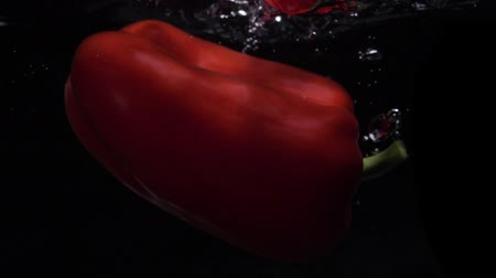 погружение : Red bell pepper falls into water. Slow motion. Black background. Food video