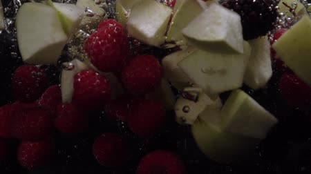 amoras : Raspberries, blueberries, blackberries and Apple pieces fall into the water on a black background. Slow motion. Organic berries, healthy food. Food video Stock Footage