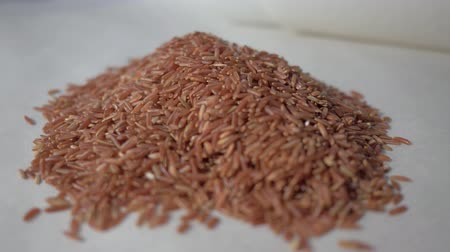 sponka : Raw red rice on the table. Concept: footage for the recipe. 4K. Food video