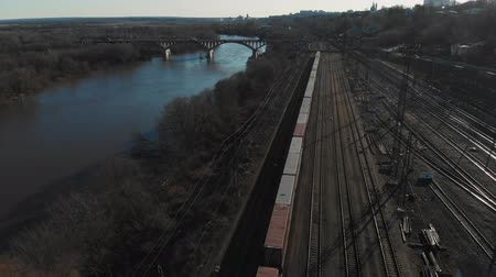 ileri : Aerial view of a large train on the rails next to the river. The camera flies over a long train of tanks standing on the rails
