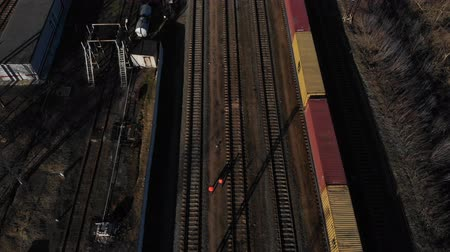 railwayman : Two railway workers are on the rails next to the standing freight train. Worker team assure railway service. Aerial view. 4K Stock Footage