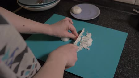 stuffing : The girl cuts a bow with a knife on a blue cutting Board. Close up. Food video 4K