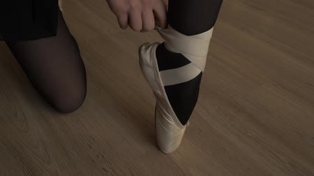 паркет : Close-up of the little ballerina wears Pointe shoes. Female feet in pointe shoes. Pointe shoes worn by ballet dancer. Ballerina shoes. Classic dance style. Стоковые видеозаписи