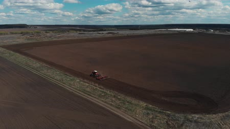 počátky : The tractor plows the ground on the field at the beginning of the planting season. Aerial view 4K Dostupné videozáznamy