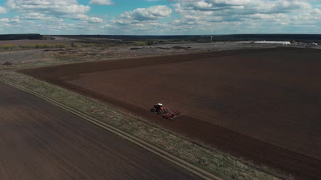beginnings : The tractor plows the ground on the field at the beginning of the planting season. Aerial view 4K Stock Footage