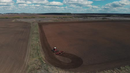 počátky : The tractor plows the ground on the field at the beginning of the planting season. The tractor turns on the field and goes to plow the land further. Aerial view 4K Dostupné videozáznamy