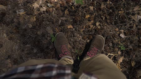 immigratie : POV View from the eyes to the feet of a man standing in place in the forest. The man is lost in the forest and does not know where to go. 4K