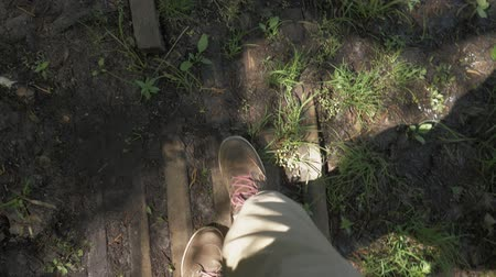 mokřady : POV The view from the eyes is like feet in brown boots with red laces walking on a swampy area. Man walking in the swamp. 4K Dostupné videozáznamy