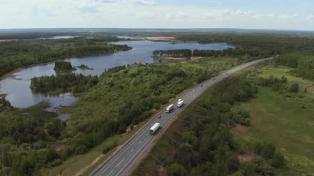 toll : Aerial View of White Truck Passing Busy highway Highway Overpass Overdrive Bridge. Cars and trucks go on the road on the background of beautiful lakes. 4K