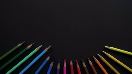 tópicos : Wooden school pencils of different colors are located on the black surface. Stop motion animation with colored pencils for use in infographics on school topics. Appearance, blinking, changing colors Vídeos