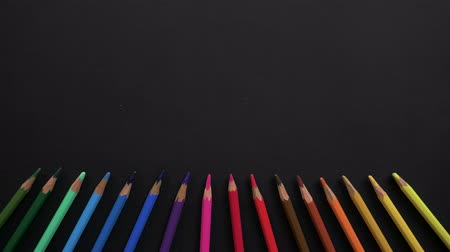 konuları : Wooden school pencils of different colors are located on the black surface. Stop motion animation with colored pencils for use in infographics on school topics. Appearance, blinking, changing colors Stok Video