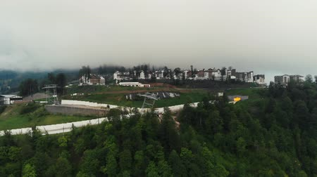 Rosa Khutor plateau, buildings, slopes and chair lifts. Aerial view at sunset, From Dron. In cloudy weather, the camera flies up to Rosa Khutor plateau Wideo