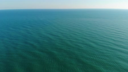 The camera flies over the sea towards the clear horizon. The cameras view rises from the sea to the clear horizon. Aerial view 4K