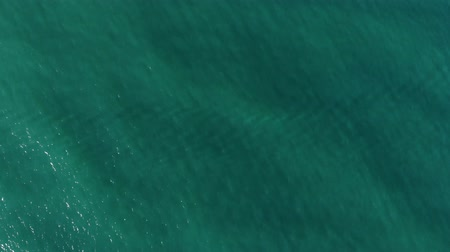 Aerial top down view from high altitude of green sea water texture. The camera flies over the water, a view of the water surface. Background of the water surface. 4K aerial view Stockvideo