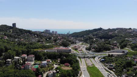 The camera flies over the city road towards the sea. Aerial view of the city, standing on the coast, from the sea. Sea view of the city beach and the city itself. The city of Sochi from the sea. 4K.