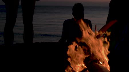 Silhouettes of a group of people with children against the sunset and the sea burning fire on the beach. Campfire on the beach