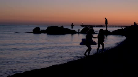Young children play on the rocks on the beach by the sea at sunset. Children play on the beach at sunset. Happy childhood by the sea. No faces