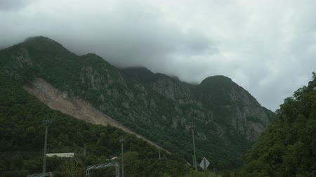 POV drive across beautiful nature with green trees and steep mountain slopes, curvy asphalt road, cloudy day Stockvideo