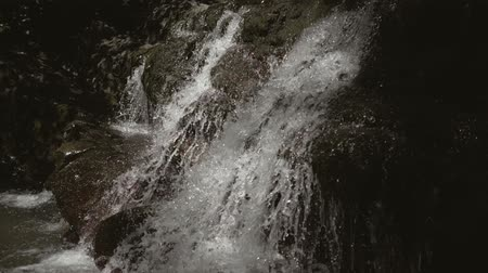 Aerial view of mountain forest waterfall. Water breaks from the rocks and falls down. Shots in slow motion of the waterfall. Slow motion shot of falling water from the waterfall