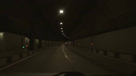 View from the car passing through the tunnel. The car passes through a long tunnel in the mountain