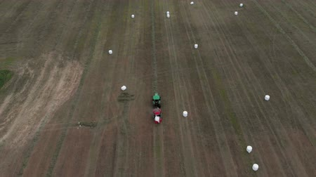 bales : Agricultural machinery rolls the crop into bales and wraps them in white packaging. Aerial view 4K Stock Footage