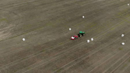 Agricultural machinery rolls the crop into bales and wraps them in white packaging. Aerial view 4K Wideo