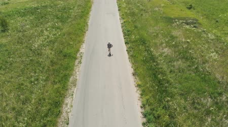 Man rides at straight road on longboard at sunset time aerial 4k. The guy rides a longboard on the way to the field, the camera follows the man