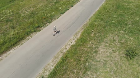 odstín : Man rides at straight road on longboard at sunset time aerial 4k. The guy rides a longboard on the way to the field, the camera follows the man