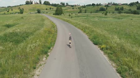 The guy goes on the road on a longboard, looks at the camera and calls with him. Follow me. The guy rides a longboard on the way to the field, the camera follows the man 4K