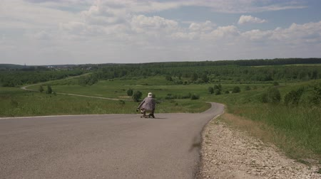 odstín : Man going down a hill on longbone in the forest Sunny summer day. Frame from a tripod, 4K
