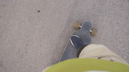Shot on a longboard from the perspective of the longboard rider (pov). Driving on the asphalt