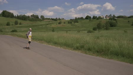 nem városi színhely : A man passes in the frame on the road on the longboard. Extreme longboard riding. Eternally young