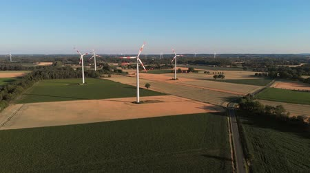 Aerial wiev of windmills farm. Power Energy Production. The camera is flying around the radius of the windmills