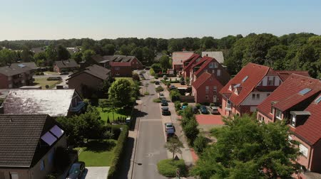 The flight of the camera over the street of a small German city. Houses with red tiled roofs. Germany, Greven. From a birds eye 4K