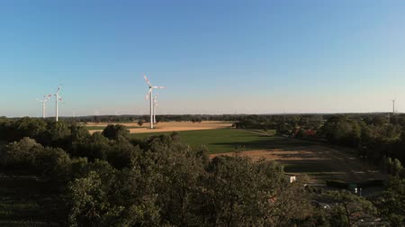 Aerial wiev of windmills farm. Power Energy Production. The camera soars above the trees and overlooks the windmills