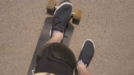 longboard : A readers down PC perspective view of a young male skateboarder on a street in a city. Look down at the injured legs of the longboarder. Longboard wound Stock Footage