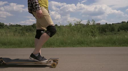 Close-up of a man in knee pads starts to go on a longboard with yellow wheels and leaves the frame