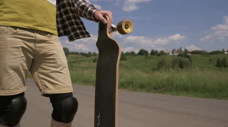 kickflip : Close-up of a man with a longboard standing in the frame. No face. 4K